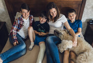 High angle view of happy mother with sons and dog sitting on bed at home - CAVF50339