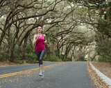 Woman jogging on road amidst trees in forest - CAVF50345