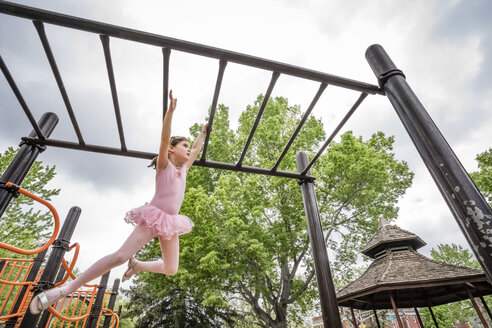 Low angle view of cute girl in ballet costume hanging on monkey bars against cloudy sky at playground - CAVF50387
