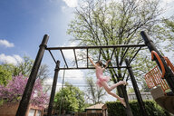 Low angle view of girl in ballet costume hanging on monkey bars against sky at playground - CAVF50390