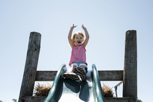 Low angle view of happy girl with arms raised sliding against clear sky at park during sunny day - CAVF50402