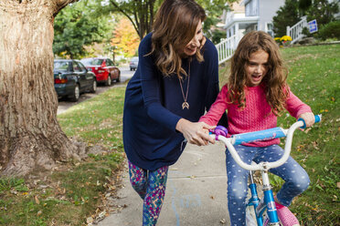 Mother assisting daughter in riding bicycle on footpath during autumn - CAVF50420