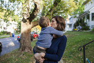 Mother kissing son while standing against trees - CAVF50423