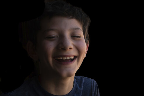Close-up portrait of happy boy laughing against black background - CAVF50441