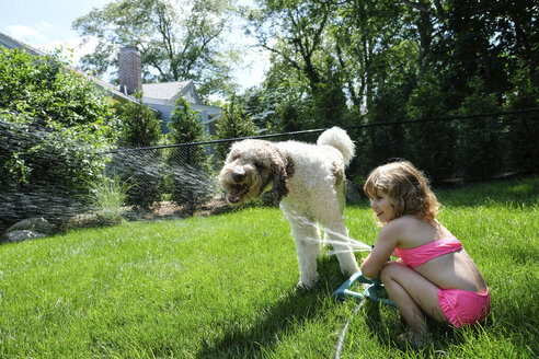 Side view of happy girl spraying water on dog with sprinkler at yard - CAVF50444