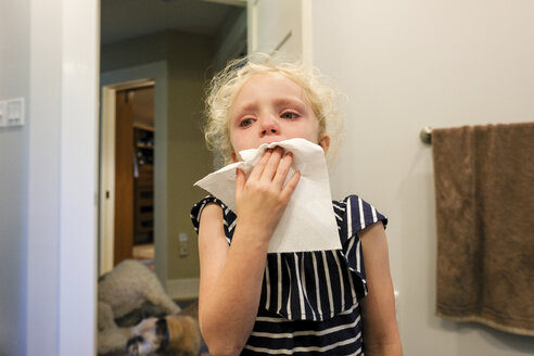 Close-up of girl crying with toothache while standing against wall at home - CAVF50447