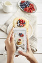 Cropped hands of woman photographing breakfast served on wooden table at home - CAVF50462