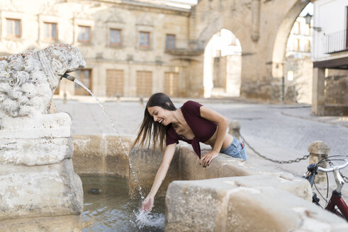 Spain, Baeza, laughing young woman splashing with water of a fountain - JASF01968