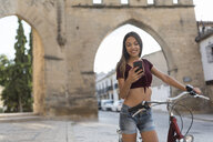 Spain, Baeza, portrait of young woman with bicycle looking at cell phone - JASF01977