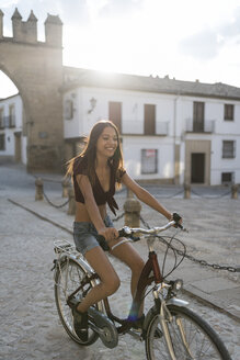 Spain, Baeza, smiling young woman riding bicycle in the evening - JASF01980