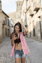 Spain, Baeza, laughing young woman looking at cell phone - JASF01983
