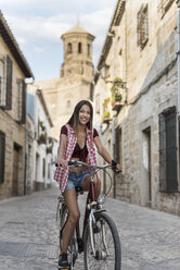 Spain, Baeza, portrait of smiling young woman riding bicycle in the city - JASF01989