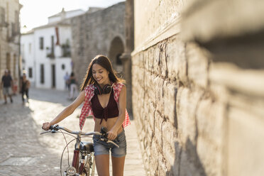 Spain, Baeza, happy young woman pushing her bicycle in the city - JASF01992