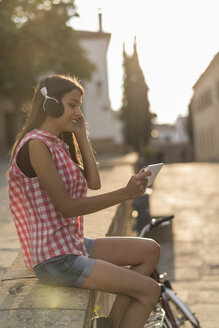Spain, Baeza, young woman relaxing with headphones and digital tablet in the evening - JASF01995