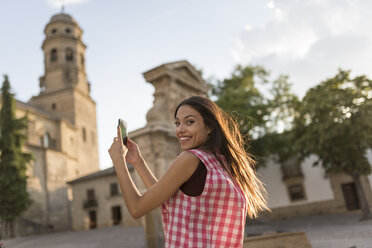 Spain, Baeza, portrait of smiling young woman taking photos with smartphone in the city - JASF01998