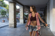 Spain, Baeza, smiling young woman with bicycle - JASF02007