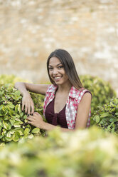 Spain, Baeza, portrait of laughing young woman relaxing in public park - JASF02013