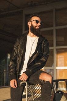Stylish bearded young man outdoors looking sideways - KKAF02488