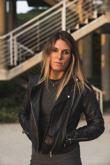 Portrait of young woman wearing a leather jacket - KKAF02500