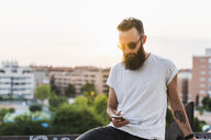 Cool bearded young man wearing sunglasses checking cell phone - KKAF02503