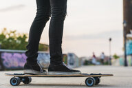 Close-up of young woman riding skateboard - KKAF02518