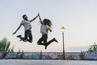 Exuberant couple jumping outdoors high fiving - KKAF02527