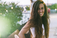 Portrait of beautiful smiling young woman with long brown hair outdoors - KKAF02530