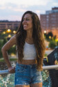 Beautiful smiling young woman with long brown hair in the city at dusk - KKAF02533