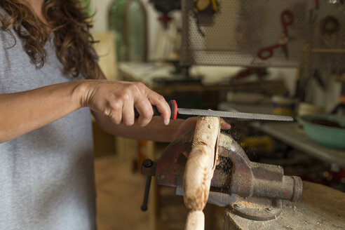 Craftswoman filing a piece of wood in her workshop - JPTF00035