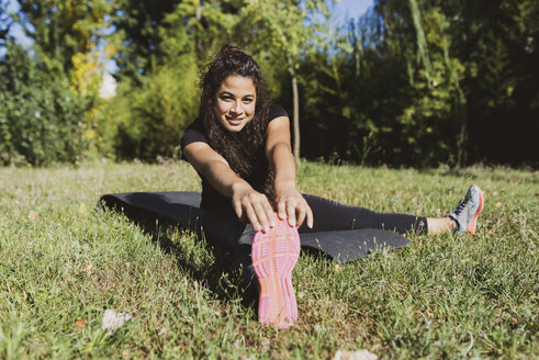 Sporty young woman stretching her leg on a meadow - FMOF00390