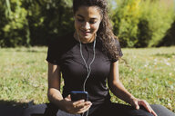 Sporty young woman having a break on a meadow - FMOF00393