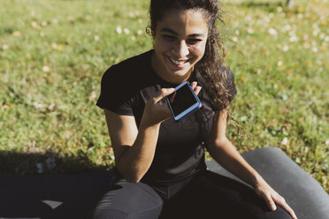Happy sporty young woman having a break on a meadow using cell phone - FMOF00396
