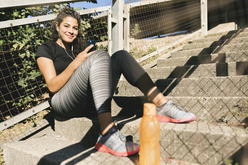 Sporty young woman having a break listening to music - FMOF00399