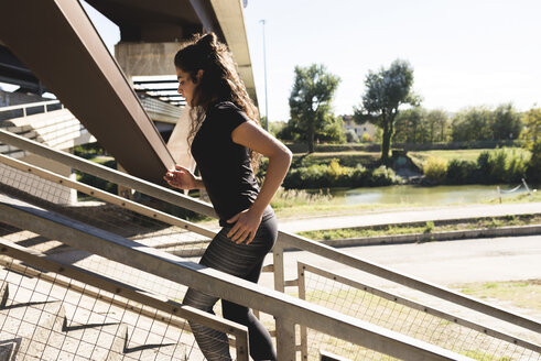 Sportive young woman running on stairs - FMOF00402