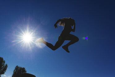 Sportive young woman jumping under blue sky in backlight - FMOF00405
