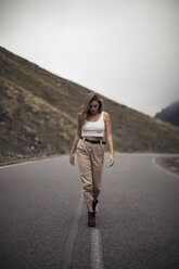 Blonde woman walking on a road, blurry person - ACPF00363