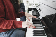 Hands of a woman playing the piano at home - KMKF00580