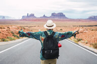 USA, Utah, Man with backpack standing on road to Monument Valley - KKAF02538