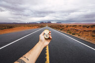 USA, Utah, Hand holding compass over road to Monument Valley - KKAF02541