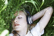 Overhead view of woman with eyes closed listening music while lying amidst grass on field - CAVF50486