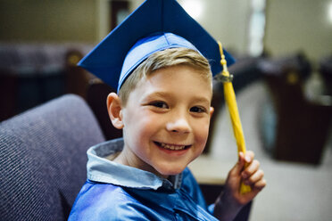 Portrait of happy boy in graduation gown siting on chair - CAVF50501
