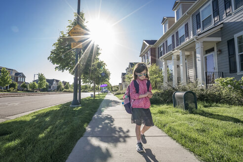 Girl with backpack wearing sunglasses while walking on footpath against clear sky during sunny day - CAVF50528