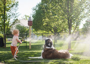 Side view of shirtless baby boy spraying water on dog with hose while standing at yard - CAVF50531