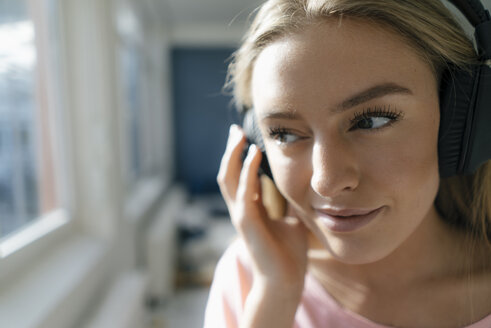 Smiling young woman listening music at home - KNSF05006