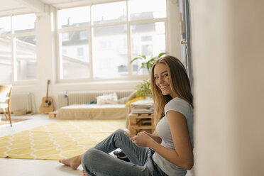 Portrait of smiling young woman sitting on the floor in her loft using smartphone - KNSF05012