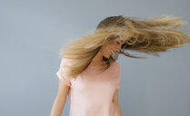 Laughing young woman tossing her hair - KNSF05015