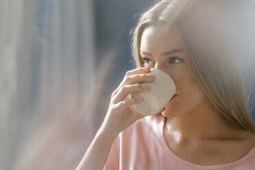 Young woman drinking cup of coffee - KNSF05021