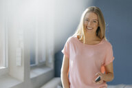 Portrait of smiling young woman with cell phone in her hand - KNSF05027