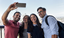 UK, London, four friends taking a selfie with city in background - MGOF03805