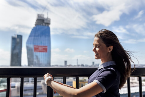 UK, London, smiling woman using smartwatch on a roof terrace - MGOF03808